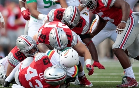 Hawaii running back Paul Harris was pounced on by Ohio State linebacker Darron Lee, bottom, defensive lineman Tommy Schutt, left, defensive lineman Joey Bosa, 97, and defensive lineman Tyquan Lewis in the first half Saturday.